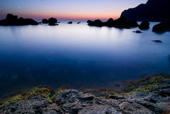 Calm blue water bay beyond the sunset Royalty Free Stock Images