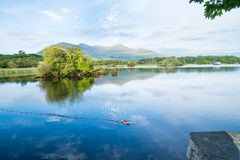 Calm blue water Ross Lake, Killarney at sunrise. Royalty Free Stock Photos