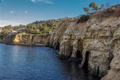 Cliffs and Caves of La Jolla, California. Calm blue waters of La Jolla Cove leading into the cliff side caves at La Jolla California royalty free stock image