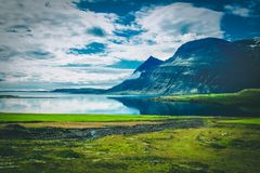 Calm Body of Water Near Black Mountain Surrounded by Green Grass Royalty Free Stock Photos