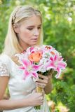 Calm bride holding her bouquet close Royalty Free Stock Photography
