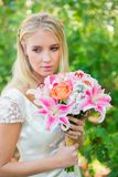 Calm bride holding her bouquet Stock Photos
