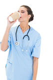 Calm brown haired nurse in blue scrubs enjoying her coffee Royalty Free Stock Images