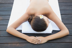 Calm brunette lying on a towel poolside Royalty Free Stock Image