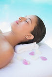 Calm brunette lying on towel with rose petals Royalty Free Stock Image