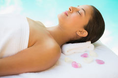 Calm brunette lying on towel with rose petals Stock Photo