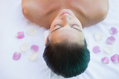 Calm brunette lying on towel with rose petals Stock Images