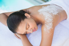 Calm brunette lying on towel with salt treatment on back Royalty Free Stock Photo