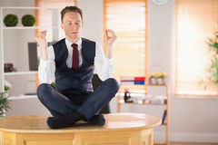 Calm businessman meditating in lotus pose Royalty Free Stock Image