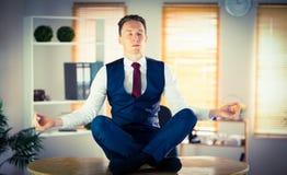 Calm businessman meditating in lotus pose Stock Images