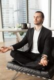 Successful businessman meditating at workplace in modern office. Calm businessman meditating in yoga lotus pose in modern office. CEO taking care of his health Stock Photography