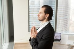 Successful businessman meditating at workplace in modern office. Stock Photo