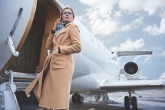 Calm businesswoman speaking by mobile near airplane stock photography