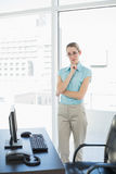Calm businesswoman standing thoughtful in her office Royalty Free Stock Photography