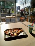 Two piece of pizza pn the plate with street view stock photography