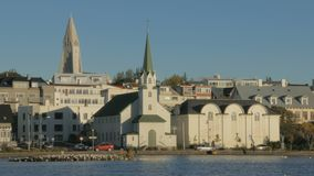 Calm car traffic near famous lake in centre in daytime in Reykjavik in sunny autumn weather. View with traditional churches stock video