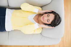 Calm casual brunette in yellow cardigan listening to music with headphones Stock Images