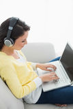 Calm casual brunette in yellow cardigan listening to music while using a laptop Stock Photo