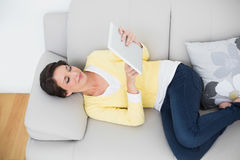 Calm casual brunette in yellow cardigan using a tablet pc Royalty Free Stock Image
