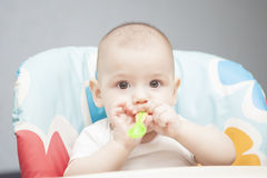 Calm caucasian infant in chair with small spoon Stock Photo