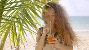 Attractive female drinking beverage beside palm tree stock footage