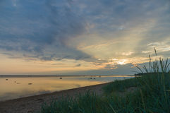 Calm and colourful cloudscape sunrise at sea gulf with tall gras Stock Photo