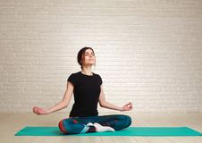 Calm and concentrated woman doing yoga exercises Stock Photos