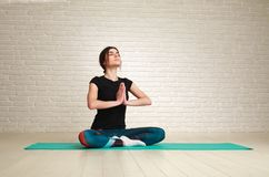 Calm and concentrated woman doing yoga exercises Stock Image