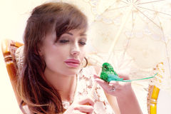 Calm conceptual portrait of attractive young lady with bird. Portrait of beautiful young brunette woman thinking with little bird on her hand Royalty Free Stock Images