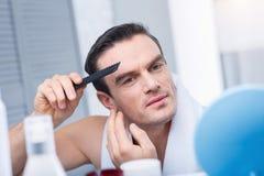 Calm confident man designing hair Stock Photos