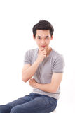 Calm, cool, confident young man sitting with hand holding chin Royalty Free Stock Photos