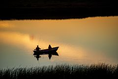 Calm countryside lake river with cloud reflections in water and green shores. Calm countryside lake river in sunset with fisherman in a boat royalty free stock images