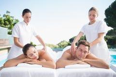 Calm couple enjoying couples massage poolside Royalty Free Stock Image