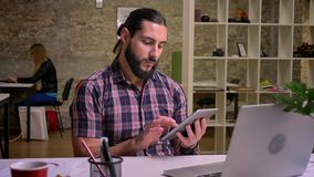 Calm creative casual caucasian male with long hair and black beard is swiping his tablet while sitting indoor at desktop. Behind laptop, brick office stock video footage