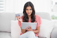 Calm cute brunette sitting on couch holding credit card and tablet Royalty Free Stock Photos