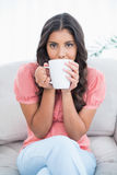 Calm cute brunette sitting on couch holding mug Royalty Free Stock Photography