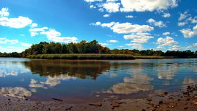 Calm day at a lake. Sky, trees and clouds reflection on lake water. Cloudy day stock video