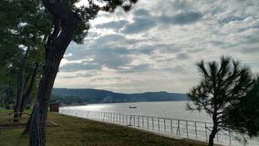 Sea coast on a calm day and cloudy sky. A calm day by the sea through the trees and cloudy sky Çanakkale royalty free stock photo