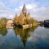A calm day with Temple Neuf reflecting over the water in Metz, France. stock photos