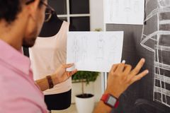 Talented designer holding sketches and drawing on the blackboard. Calm designer. Clever professional designer working in the atelier and carefully holding a new stock photos