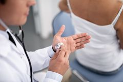 Calm doctor putting stethoscope on his hand stock photos