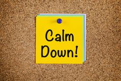 Calm Down! on corkboard. Paper notes with words Calm Down! on cork board stock photo