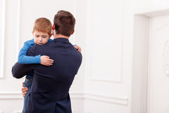 Calm down my pretty little loving child. Young businessman has to go to work. He is holding his son and embracing. The boy is crying with despair. Copy space in Stock Photo