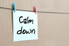 Calm down. Note is written on a white sticker that hangs with a. Clothespin on a rope on a background of brown cardboard royalty free stock image