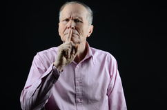 Calm down. Senior with his finger up close to his mouth Royalty Free Stock Images