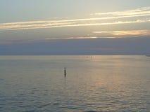 Calm evening sea, sunset clouds. Marine sunset, mauve clouds and sunbeams stock photos