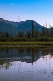 Calm evening at Vermillion Lakes. A crescent moon can be seen in the early evening at Vermillion Lakes in Banff National Park royalty free stock images