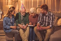 Calm family thinking of old times. Serene granny pointing finger on frame while sitting near grandfather, female and man on sofa. Memory concept royalty free stock image