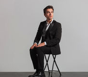 Calm fashion model in tuxedo sitting on chair Royalty Free Stock Images
