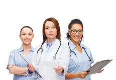 Calm female doctor with clipboard. Healthcare and medicine concept - calm female doctor adn nurses with clipboard and stethoscope giving prescription Royalty Free Stock Photo